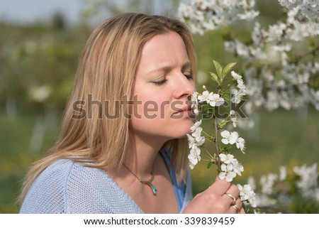 Young beautiful woman smelling blooming flowers of plum tree - stock photo