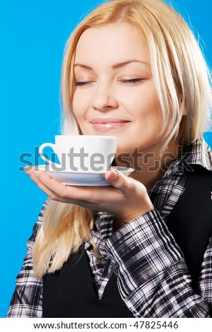 Young beautiful woman smelling coffee, blue background - stock photo