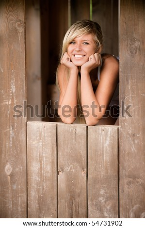 Young beautiful woman smiles from shed - stock photo