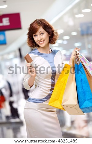 Young beautiful woman smiles in shop with bags and a credit card - stock photo
