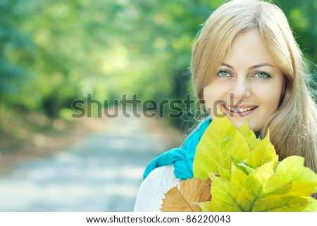 Young beautiful woman smiling and holding yellow leaves against blurred early autumn background with copy space - stock photo