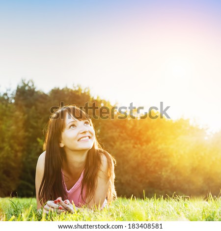Young beautiful woman smiling and lying on the grass at summer sunset looking at the sky. Natural happiness, fun and harmony. - stock photo