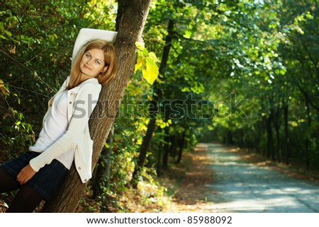 Young beautiful woman smiling leaning against tree with blurred early autumn background and copy space - stock photo