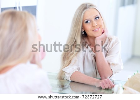 Young beautiful woman smiling to herself in mirror - stock photo
