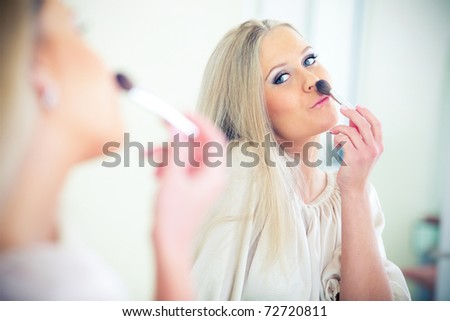 Young beautiful woman smiling to herself in mirror