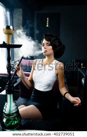 Young, beautiful woman smokes a hookah in cafe. It produces smoke from his mouth. Business style clothing. The pleasure of smoking.  - stock photo