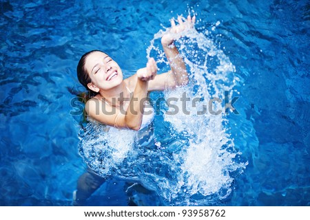 Young beautiful woman splashing water in swimming pool - stock photo