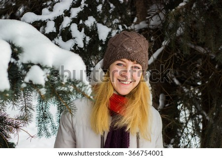 Young beautiful woman stand behind the trees in winter season - stock photo