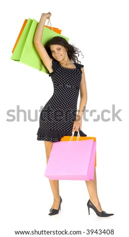Young, beautiful woman standing and holding bags. Smiling and looking at camera. Isolated on white in studio. Hand up, whole body