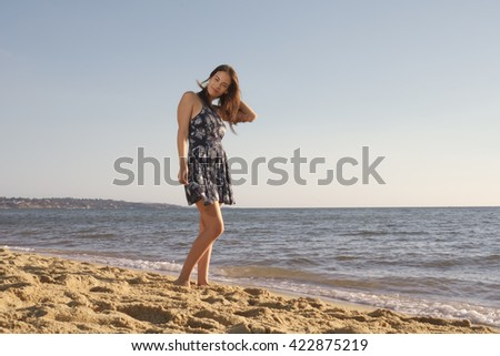 Young beautiful woman standing in short dress on the sandy beach in relaxing pose holding her hair with water in background