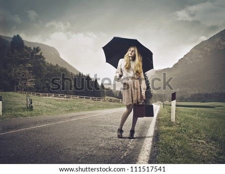 Young beautiful woman standing on a country street under an umbrella - stock photo