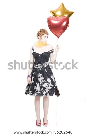 Young beautiful woman standing with golden star-shape and red  helium balloon, isolated on white background