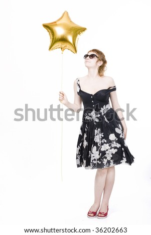 Young beautiful woman standing with golden star-shape helium balloon, isolated on white background