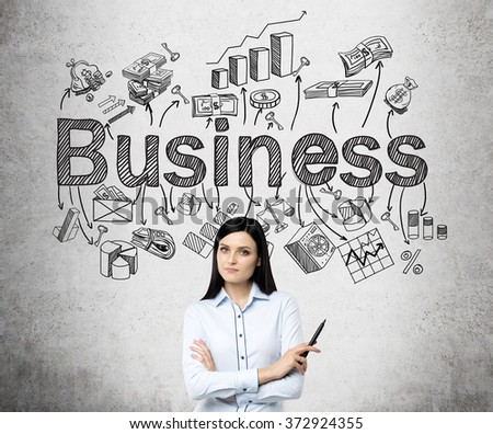 young beautiful woman standing with hands crossed and holding a pen, the word 'business' and numerous business symbols over her head. Concrete background. Concept of developing a business. - stock photo