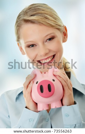 Young beautiful woman standing with piggy bank (money box).
