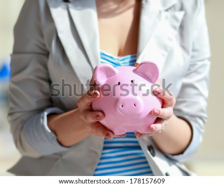 Young beautiful woman standing with piggy bank (money box), on building