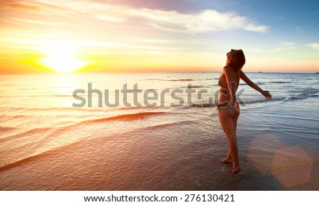 Young beautiful woman stands towards the sun on Sea beach during a amazing sunset. - stock photo