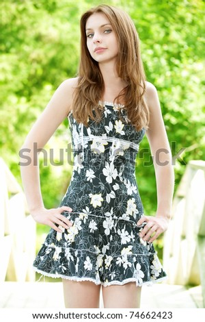 young beautiful woman staying on natural background - stock photo