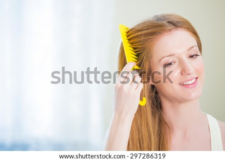 Young beautiful woman straightening her long hair
