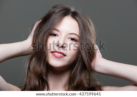 Young beautiful woman straightens her hair. Studio portrait, close-up. - stock photo