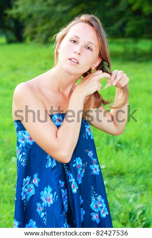 Young beautiful woman straightens her hair. Summertime in nature - stock photo