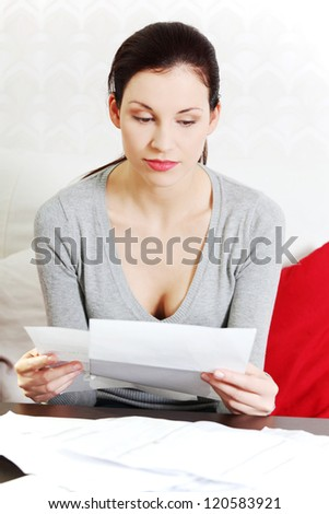 Young beautiful woman stressed because of bills. - stock photo