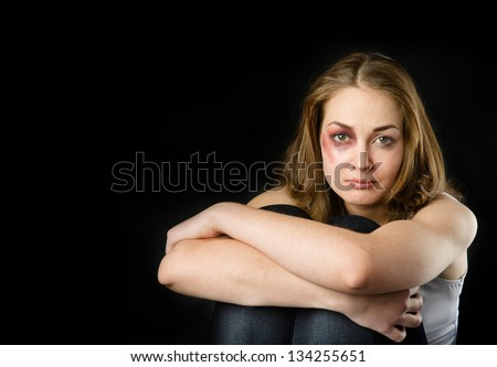 Young beautiful woman suffering from a severe depression. isolated on dark background - stock photo