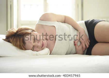 young beautiful woman suffering stomach cramps on belly holding tummy with her hands in period pain lying on bed at home bedroom in soft lifestyle lighting set in menstruation hurt concept - stock photo