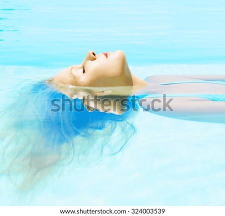 Young beautiful woman swimming water in swimming pool - stock photo