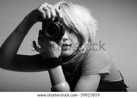 Young beautiful woman taking a photo with a digital camera