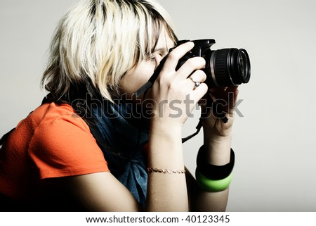 Young beautiful woman taking a photo with a digital camera - stock photo