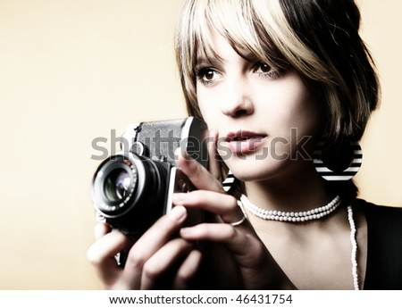 Young beautiful woman taking a photo with a retro camera