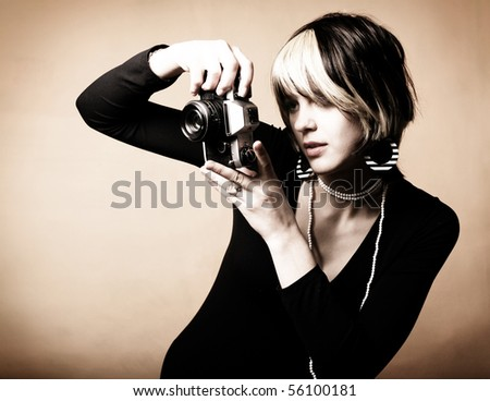 Young beautiful woman taking a photo with a retro camera - stock photo