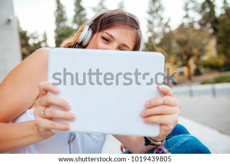 Young Beautiful Woman Taking A Photo With A Tablet