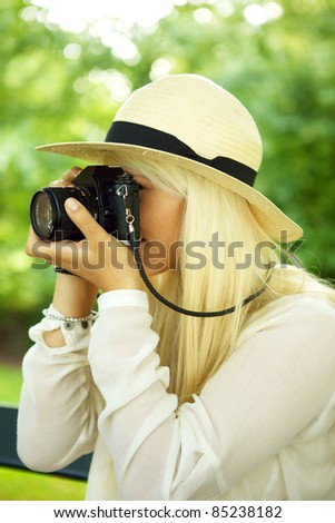 Young beautiful woman taking a picture in a park. - stock photo