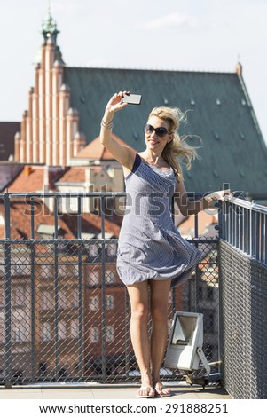 Young beautiful woman taking pictures of himself on a smartphone on the observation platform of the Castle Square in Warsaw, Poland. - stock photo