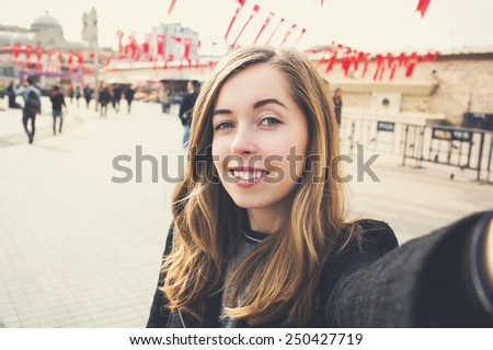 Young beautiful woman taking selfie near turkish flags at Taksim Square in Istanbul, Turkey - stock photo