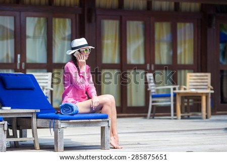 Young beautiful woman talking by phone at tropical resort - stock photo