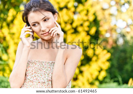 Young beautiful woman talks by mobile phone, against autumn nature. - stock photo