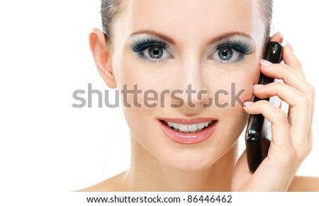 Young beautiful woman talks by mobile phone and smiles, isolated on white background. - stock photo