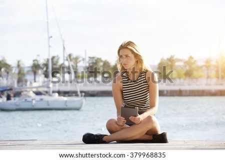 Young beautiful woman thinking about something after reading electronic book on her portable touch pad, dreaming female looking away while sitting with digital tablet on a wooden pier near sea port