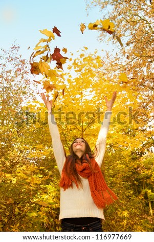 Young beautiful woman throwing the yellow leafs in the air - stock photo