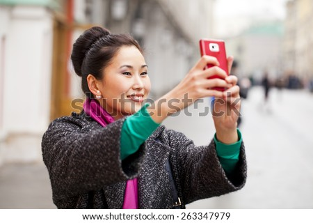 Young beautiful woman tourist taking pictures on mobile phone on the background spring street - stock photo