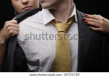 young beautiful woman undresses a man in a suit - stock photo