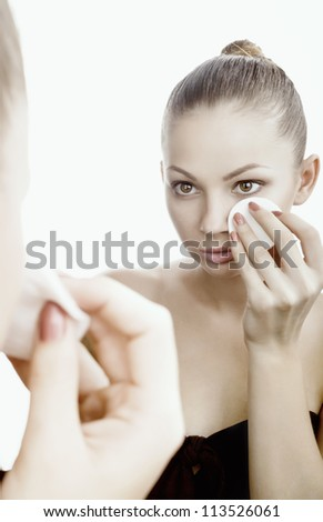 Young beautiful woman using a cotton pad to remove her make-up - stock photo