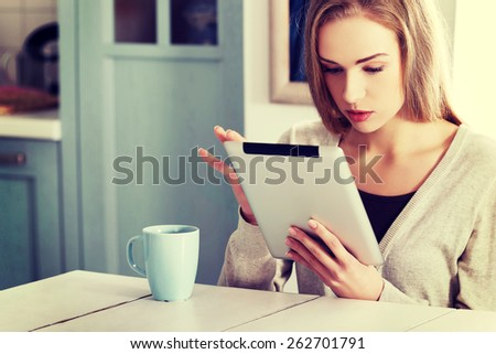 Young beautiful woman using a tablet computer at home - stock photo