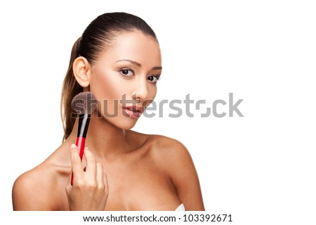 Young beautiful woman using brush to apply makeup isolated on white - stock photo