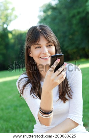 Young beautiful woman using cell phone outdoor - stock photo