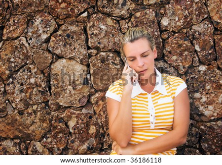 Young beautiful woman using her mobile phone in front of a highly textured stonewall - stock photo