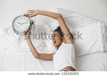 Young beautiful woman waking up in the morning. Alarm clock ringing. - stock photo